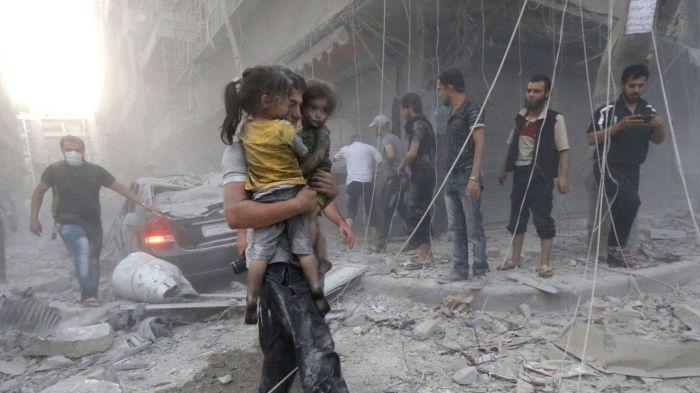 un-homme-porte-deux-fillettes-dans-ses-bras-apres-un-bombardement-du-regime-syrien-le-9-juillet-2014-a-alep_5162585.jpg