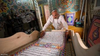 Saad Mohammed rolls down what he says is the largest handwritten version of Koran in the world measuring around 700 meters long, the town of Belqina, north of Cairo, Egypt, April 26, 2017. Picture taken April 26, 2017. REUTERS/Mohamed Abd El Ghany